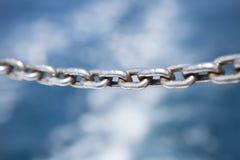 Cadena fuerte del hierro con el fondo borroso del océano Imágenes de archivo libres de regalías