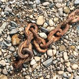 Cadena oxidada en una playa de guijarros Imagen de archivo libre de regalías