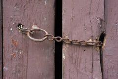 Cadena oxidada en una puerta de granero vieja Foto de archivo libre de regalías