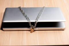 Cadena pesada con un candado alrededor de un ordenador portátil en la tabla imagenes de archivo