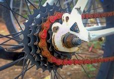 Cadena-rueda oxidada roja y bicicleta vieja blanca Fotografía de archivo