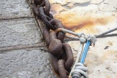 Cadena vieja para las anclas del barco en la costa imagenes de archivo