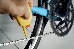 Cadena y engranaje de engrase de la bicicleta del mecánico con aceite fotos de archivo