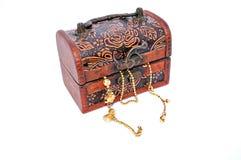 Cadenas del oro en una caja de madera tallada cerrada del tesoro Foto de archivo libre de regalías