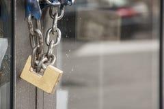 Cadenas et chaîne en laiton sur une porte en verre Photos libres de droits