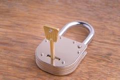 Cadenas fermé de vieux type avec la clé sur le Tableau en bois Photographie stock libre de droits