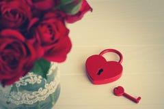 Cadenas rouge en forme de coeur avec la clé et le bouquet des roses Photo libre de droits