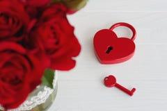 Cadenas rouge en forme de coeur avec la clé et le bouquet des roses Photographie stock libre de droits