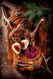 Cadera asada de la carne de venado con las peras en la bandeja de madera imagen de archivo