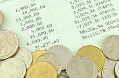 Caderneta bancária de cliente da economia com moedas tailandesas Imagem de Stock Royalty Free