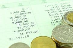 Caderneta bancária de cliente da economia com moedas tailandesas Fotos de Stock