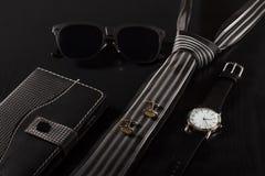 Caderno, óculos de sol, laço, botão de punho, relógio em um backgrou preto Imagem de Stock Royalty Free