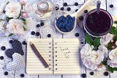 Caderno aberto com amor do texto você, rosas selvagens, doce no frasco do vintage e baga fresca na colher Fotografia de Stock Royalty Free