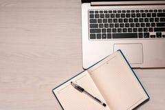 Caderno aberto com pena preta e o portátil de prata em uma tabela de madeira branca, vista superior, spase da cópia imagens de stock