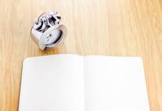 Caderno aberto da placa com o despertador de prata ao lado dele em de madeira fotografia de stock royalty free