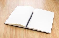 Caderno aberto da placa com o lápis preto na tabela de madeira, tem do negócio imagens de stock royalty free