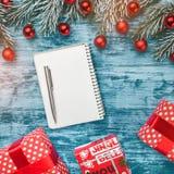 Caderno aberto da placa com quinquilharias do Natal, ramos do abeto e caixas de presentes Configuração lisa, vista superior imagens de stock