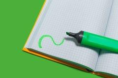 Caderno aberto e um marcador em uma superfície verde foto de stock royalty free