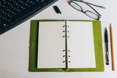 Caderno aberto na pena e no lápis da vitória da tabela fotografia de stock royalty free