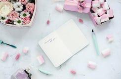 Caderno aberto na tabela branca com flores e marshmallow Árvore congelada sozinha Configuração lisa foto de stock