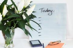 Caderno alaranjado, glassses, eBook azul com PLANOS PARA a mesa de HOJE e um ramalhete de lírios brancos bonitos na tabela branca foto de stock royalty free