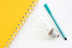 Caderno amarelo com lápis e lightblub verdes Foto de Stock Royalty Free