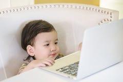 Caderno asiático do computador do uso da criança do close up para desenhos animados do relógio no fundo da casa Fotografia de Stock Royalty Free