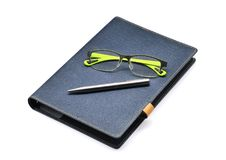 Caderno azul com vidros verdes e prata pe0n isolado Fotos de Stock Royalty Free