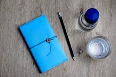 Caderno azul, lápis, vidro da água e garrafa de vidro fotos de stock