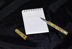 Caderno branco com uma pena dourada em um fundo preto imagem de stock royalty free