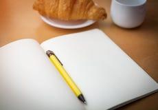 Caderno branco e pena amarela com o croissant na tabela de madeira Fotos de Stock Royalty Free