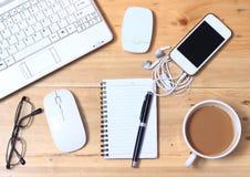 Caderno branco, modem, fone de ouvido, Smartphone, monóculo, café, rato sem fio na mesa de madeira, configurações lisas ou vista  imagem de stock