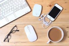 Caderno branco, modem, fone de ouvido, Smartphone, monóculo, café, rato sem fio na mesa de madeira, configurações lisas ou vista  fotografia de stock royalty free