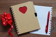 Caderno com coração vermelho e um presente em uma tabela de madeira Imagem de Stock