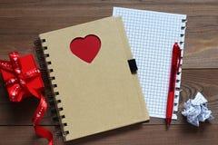 Caderno com coração vermelho e um presente em uma tabela de madeira Foto de Stock Royalty Free