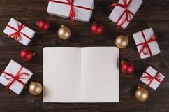 Caderno com decoração do Natal e presentes no fundo de madeira Para fazer a lista, conceito da letra de Santa Vista superior, con Imagens de Stock