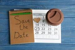 """Caderno com inscrição \ """"economias a data \"""", calendário e copo no fundo de madeira da cor imagens de stock royalty free"""