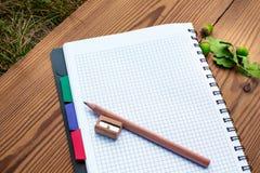 Caderno com lápis, apontador e arcons Fotografia de Stock