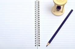 Caderno com lápis e vidro do tempo Fotografia de Stock