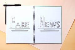 Caderno com NOTÍCIA FALSIFICADA das palavras no fundo da cor fotografia de stock