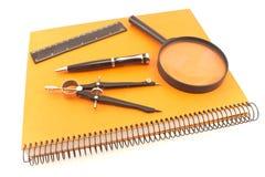 Caderno com o compasso, a régua e a lente de aumento de desenho isolados em w Imagem de Stock