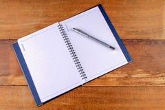 Caderno com a pena em tabelas de madeira velhas Foto de Stock