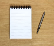 Caderno com a pena na mesa de madeira Fotos de Stock Royalty Free