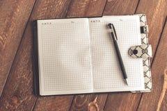 Caderno com a pena na tabela de madeira velha foto de stock