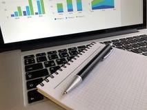 Caderno com a pena no teclado do portátil fotos de stock royalty free