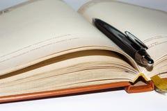 Caderno com a pena preta do escritório Imagem de Stock