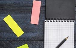 caderno com uma folha em uma gaiola com lápis e notas pegajosas coloridas em um fundo rústico de madeira, fim acima, vista superi Imagem de Stock Royalty Free