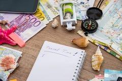 caderno com vara do selfie, dinheiro, vidros, mapa, conchas do mar, compasso Fotos de Stock