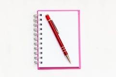 Caderno cor-de-rosa com o isolado vermelho da pena Imagem de Stock Royalty Free