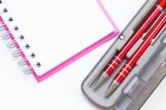 Caderno cor-de-rosa com a pena de dois vermelhos na caixa no fundo branco Imagens de Stock